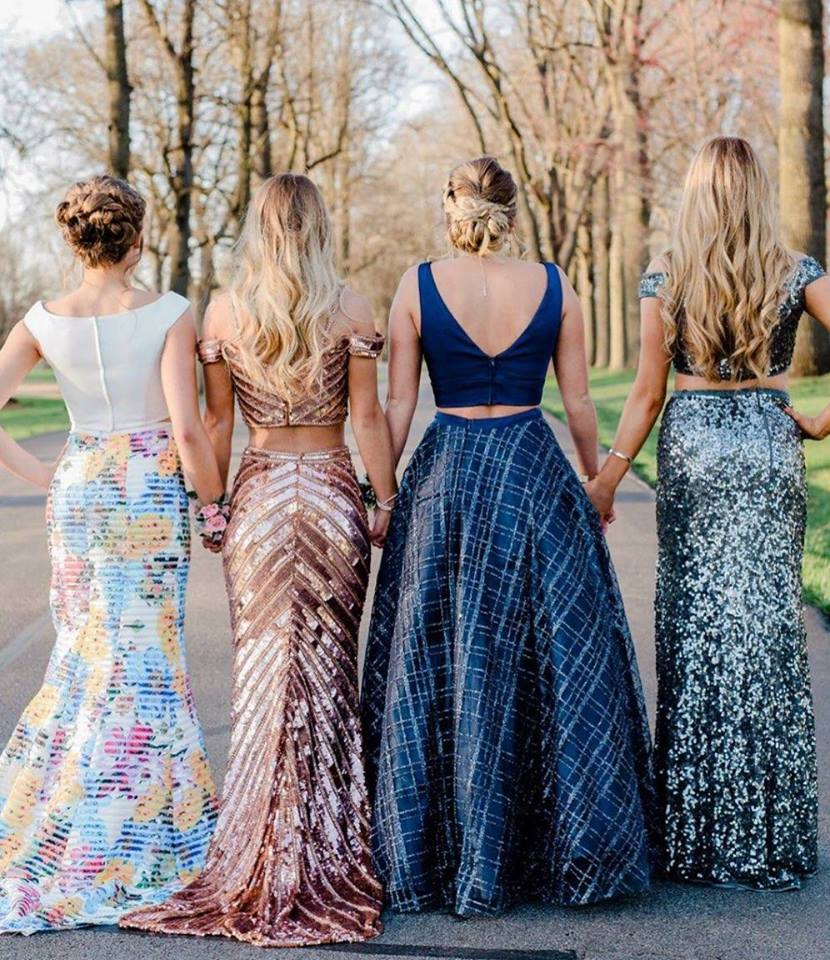 The back of four girls holding hands, wearing prom dresses.