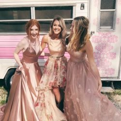 Three girls wearing blush pink homecoming dresses, smiling and laughing.