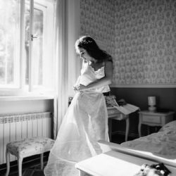 Black and white image of a bride putting on a slip undergarment