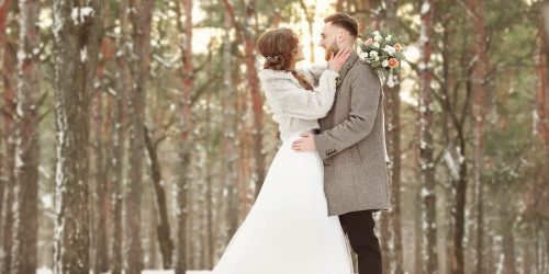Bride and groom hugging in snowy winter forest