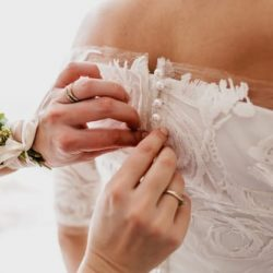 Hands buttoning up a wedding dress with lace details and pearl buttons.