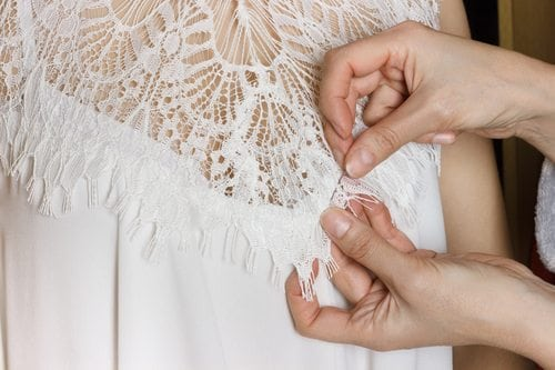 A seamstress prepares a wedding dress during a fitting.
