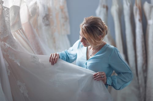 Girl in blue blouse examining a wedding dress in a bridal salon.