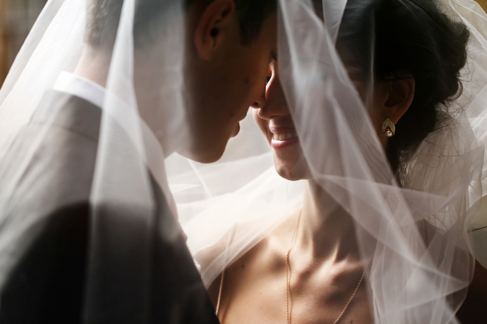 Bride and groom smiling under veil, noses touching
